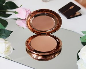 Charlotte tilbury airbrush bronzer sit open on a mirror surrounded by flowers.