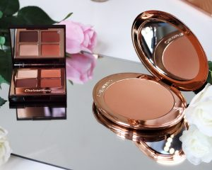 Charlotte tilbury airbrush bronzer and desert haze eyeshadow palette sit open on a mirror surronded by flowers.