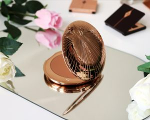 Charlotte tilbury airbrush bronzer sits open on a mirror surrounded by flowers. The bronzer is turned to the side so we can see the casing.