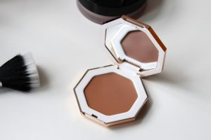 Fenty cream bronzer sits open on a white table.