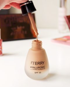 A bottle of By Terry Hyaluronic hydra foundation sits on a table surrounded by makeup. The lip has a dropper and it's being held above and squeezed, some foundation is dropping out into the bottle below.