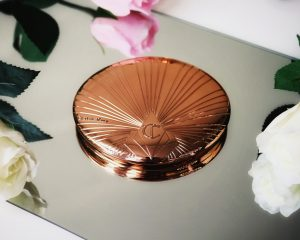 Charlotte Tilbury Airbrush Bronzer sits on a mirror showing off it's beautiful packaging which is rose gold metal and vintage in style.