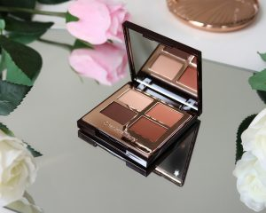 Desert Haze eyeshadow palette sits on a mirrored surface open so we can see the shade range which are warm, earthy browns.