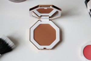 Fenty Beauty's cream bronzer sits open, on a white table