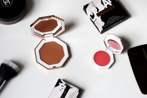 Fenty cream bronzer and blushers are laid with their boxes on a white table.