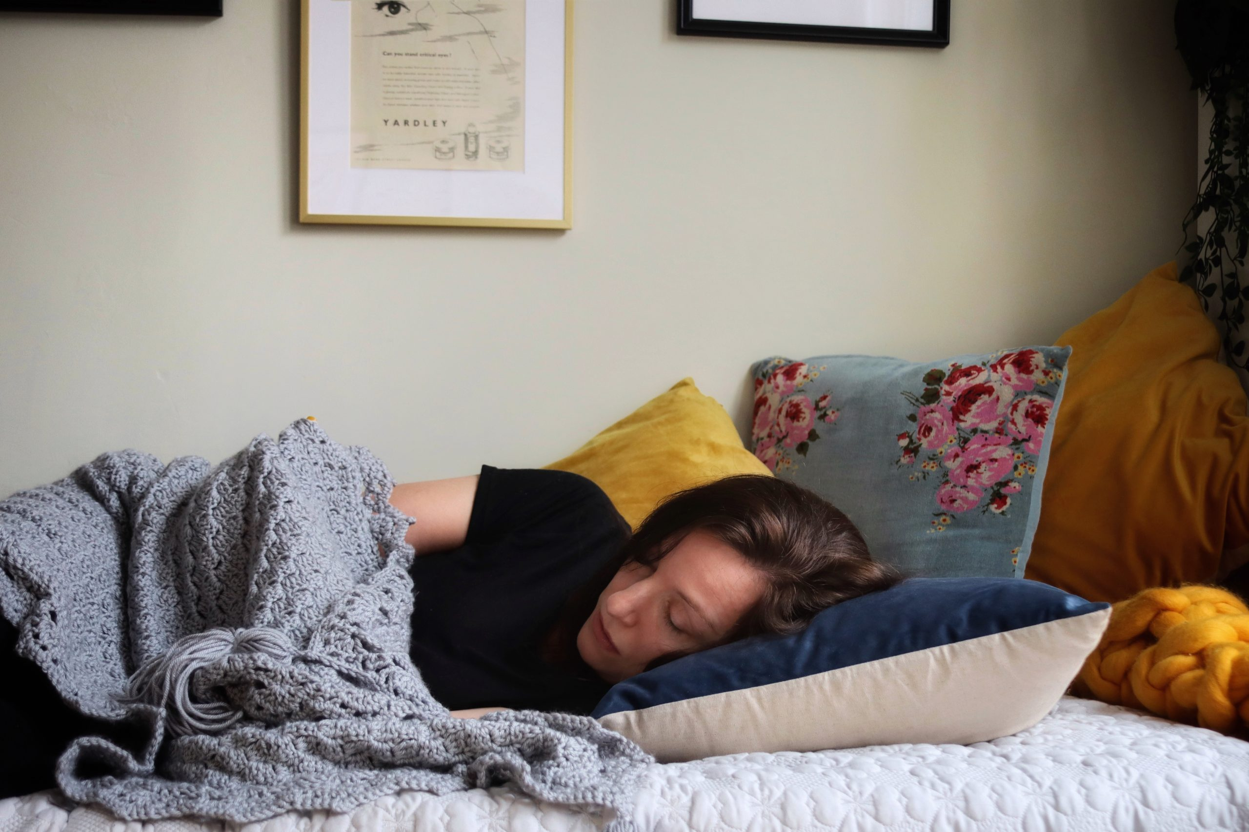 Amy lies on her bed covered in a blanket. She is surrounded by cushions. She is sick with MECFS.