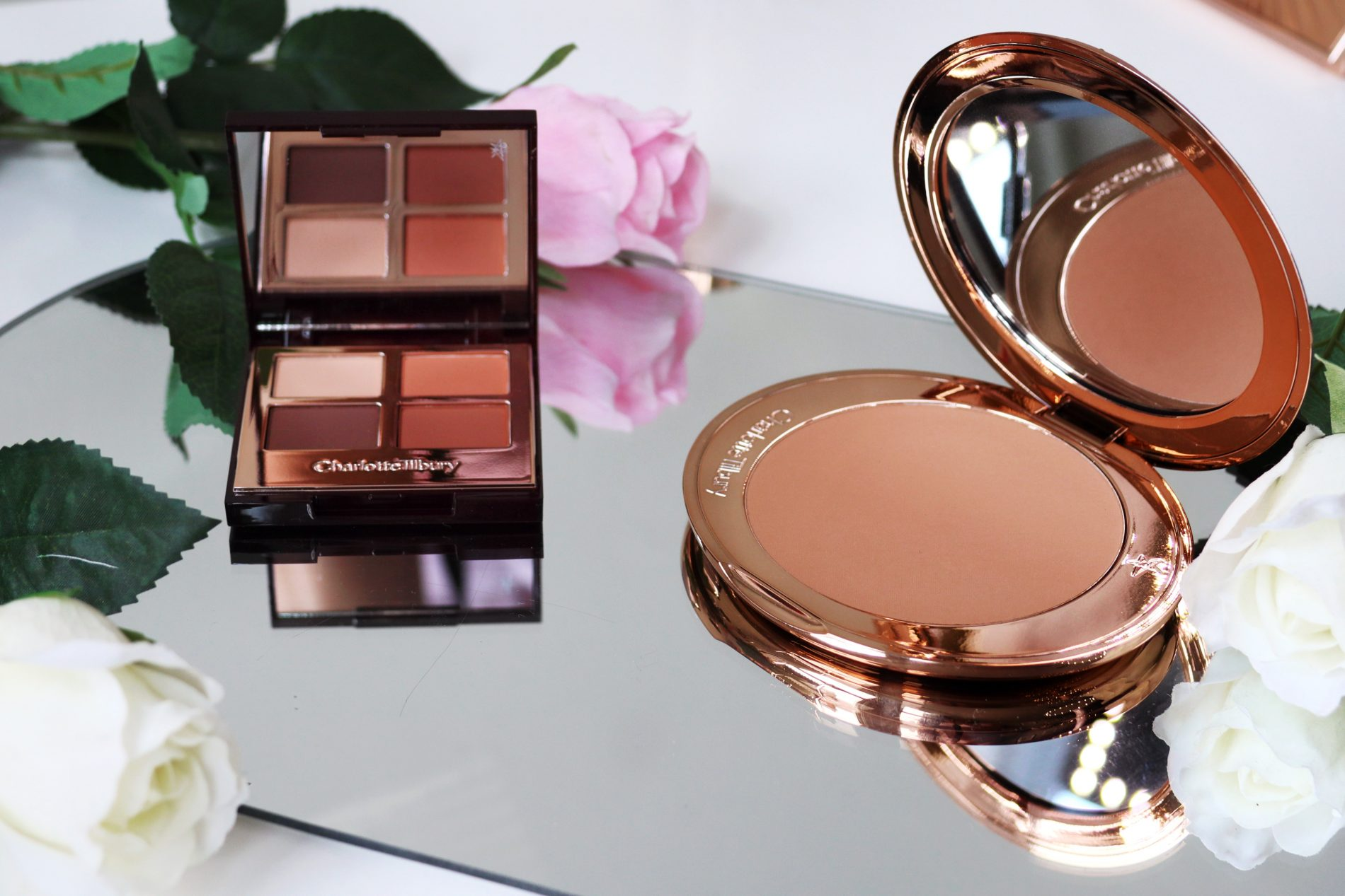 Charlotte tilbury airbrush bronzer and desert haze eyeshadow palette sit open on a mirror surrounded by flowers.