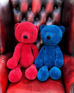 Two Crochet teddy bears, one red and one blue sit on an arm chair.