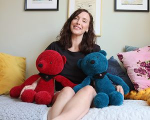 Large crochet teddy bears sat with Amy for size reference