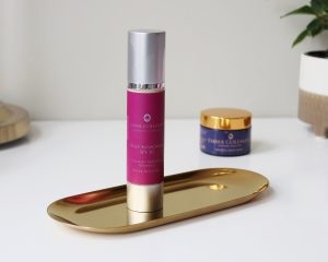 Emma Coleman Skincare Daily sunscreen SPF50 stands on a golden tray. The SPF is in a silver tube with a purple label showing the logo.