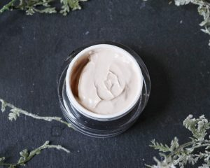 A pot of Matis Paris face cream is open to show the texture of the cream