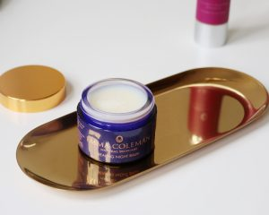 A tub of natural healing night balm sits open on a golden tray to show the texture of the product