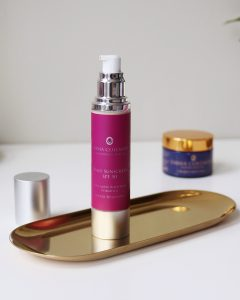 Emma Coleman Skincare Spf50 stands on a desk for review. The tube is silver and the logo purple.