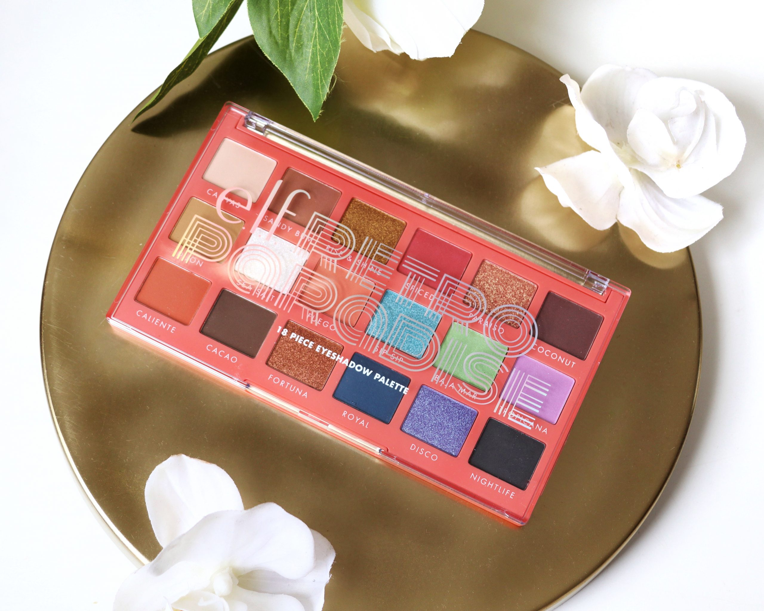 ELF Retro Paradise Eyeshadow Palette sits on a gold tray surrounded by white flowers