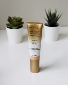 Maxfactor Second Skin Foundation in a tube stands on a table for this review