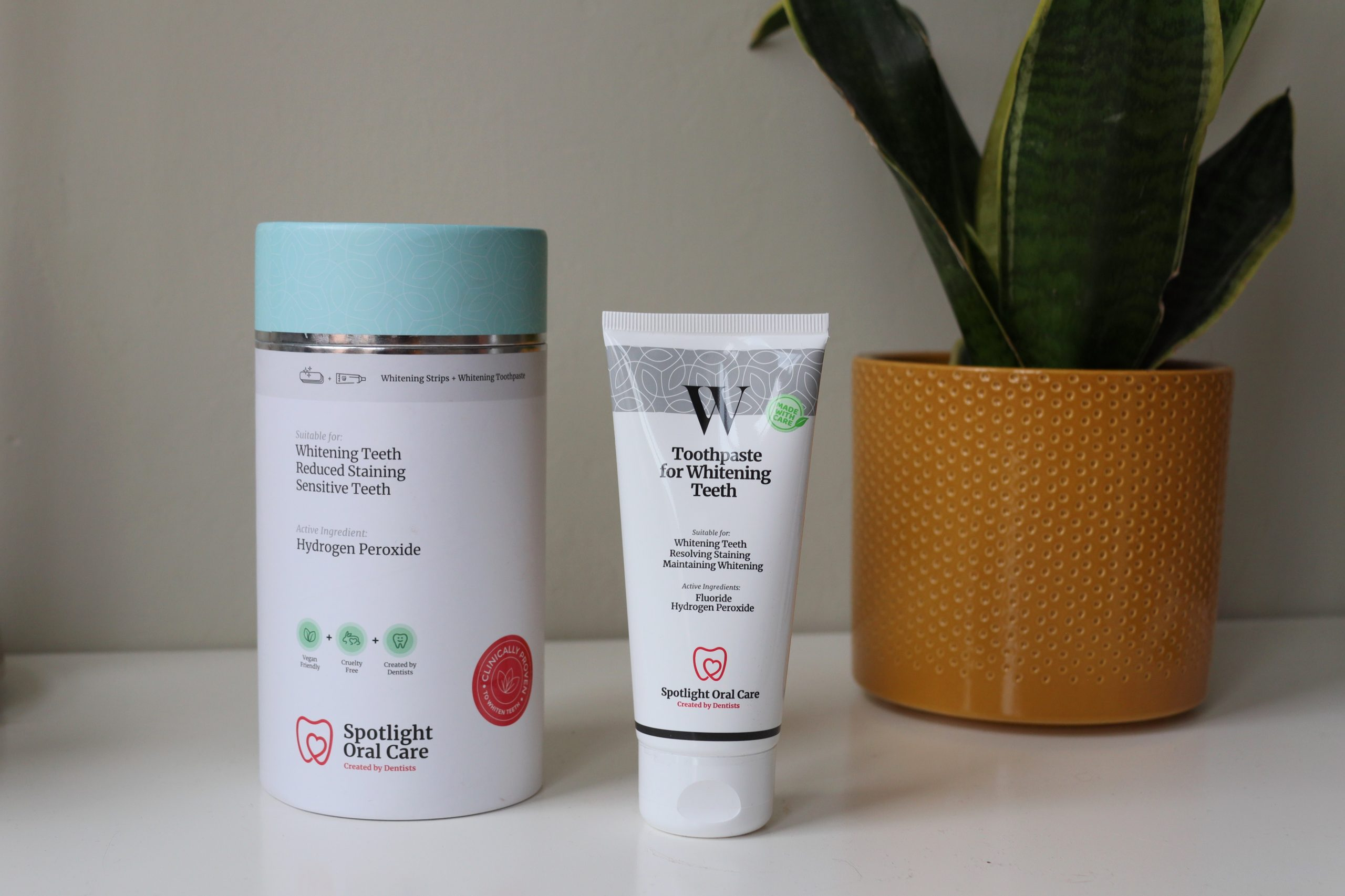 Spotlight Teeth Whitening System, a toothpaste and the container stand on a desk for this review