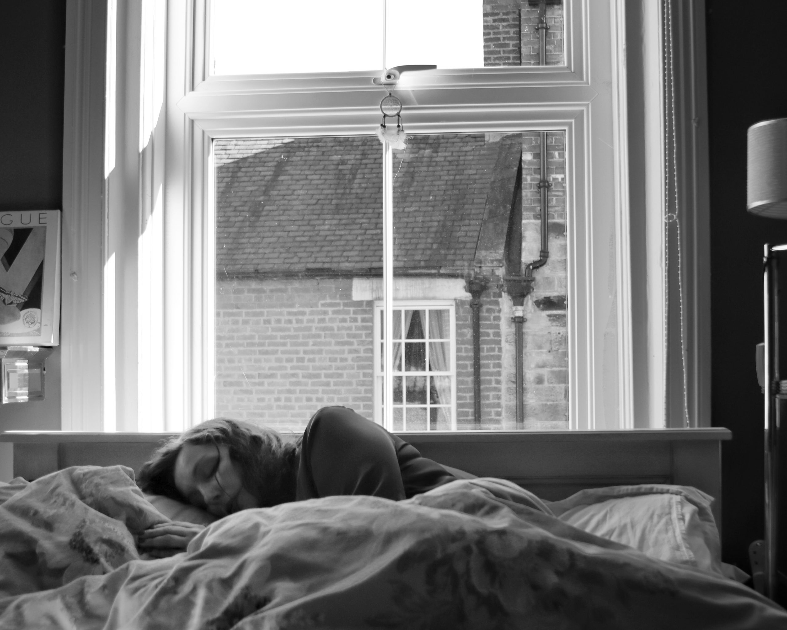 Amy lies in her bed. She has severe ME/CFS. There is a window behind the bed.