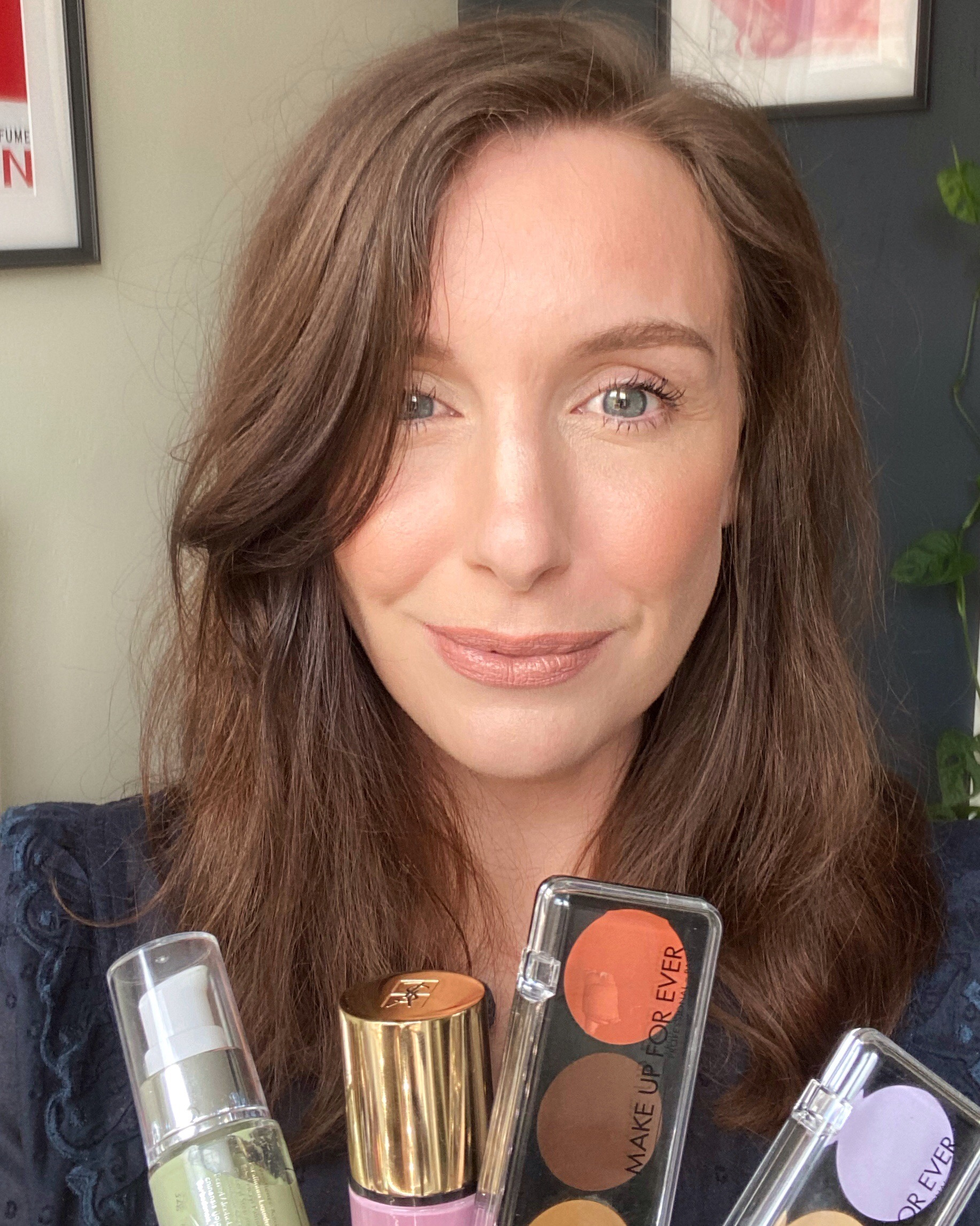 Amy smiles holding varies colour correcting makeup