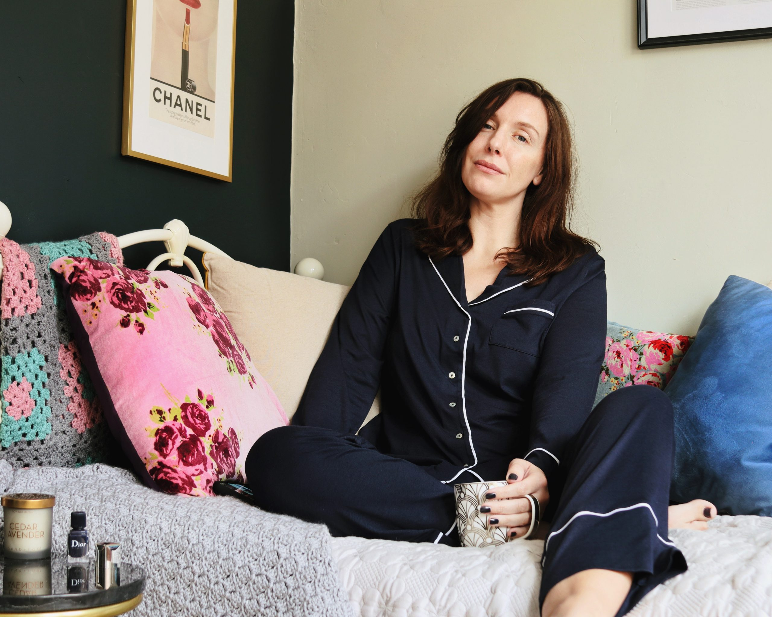 Amy is sat on her day bed, supported by cushions. She wears blue pj's and is looking knowingly towards the camera contemplating the thoughts being discussed in the post of medical neglect and gaslighting.