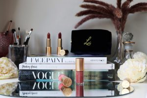 Lisa Eldridge Beauty Holiday 2020 includes gloss embrace lip gloss and true velvet lipsticks. They stand on top of beauty books on a makeup vanity.