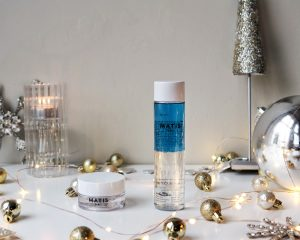 Eye cream and eye makeup remover stand on a desk surrounded by Christmas baubles and candles to create a christmas feel