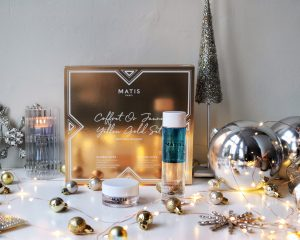 Matis Paris Yellow Gold Set sits on a desk surrounded by Christmas directions. It is a skincare gift set.