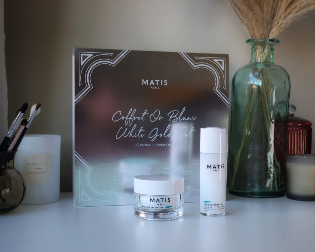 Matis Paris The White Gold Set skincare cruelty free. A pot of moisturiser and a serum stand on a marble top to be reviewed in this blog post