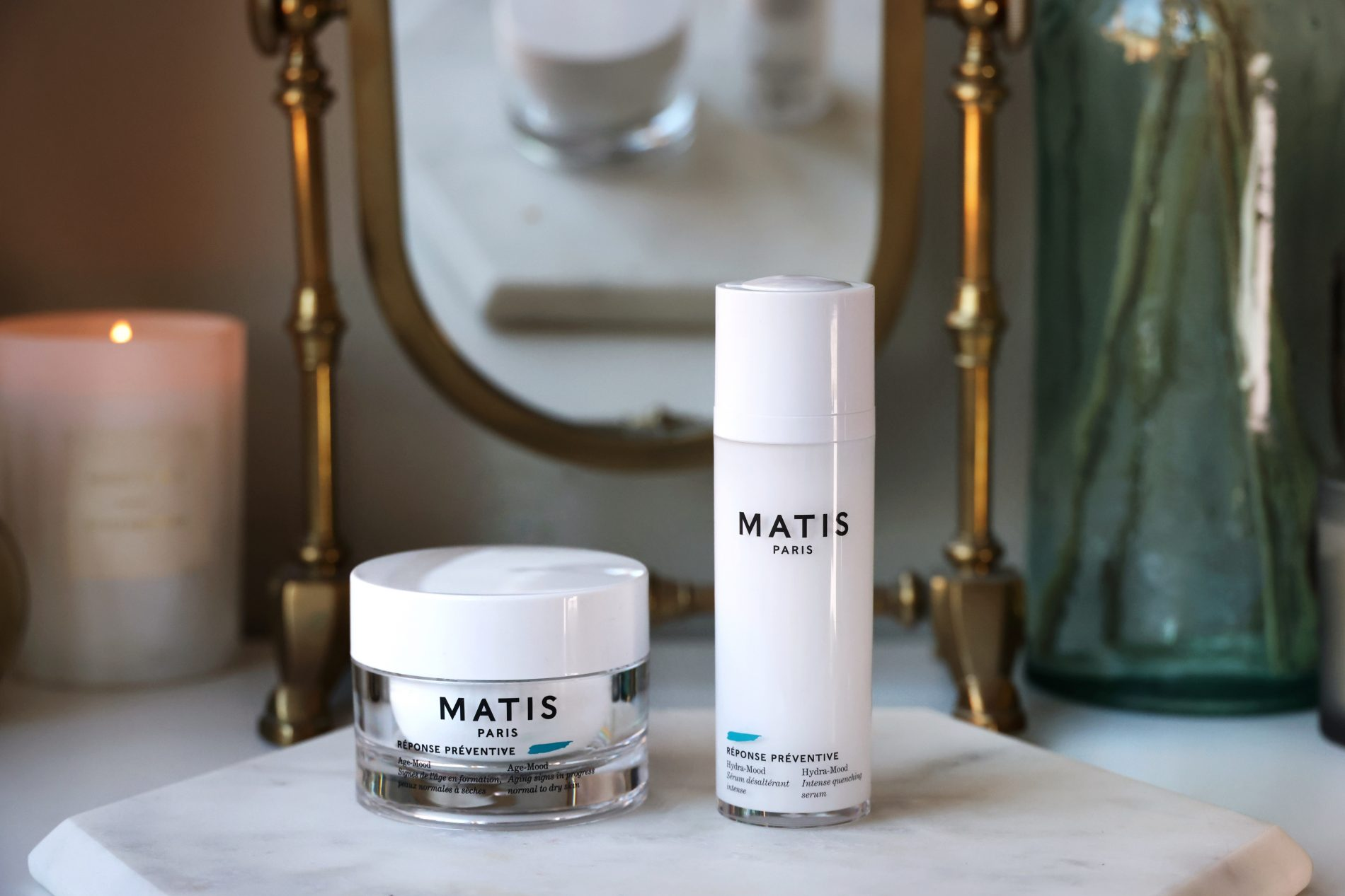 Matis Paris The White Gold Set skincare cruelty free. A pot of moisturiser and a serum stand on a marble top in front of a gold mirror to be reviewed in this blog post