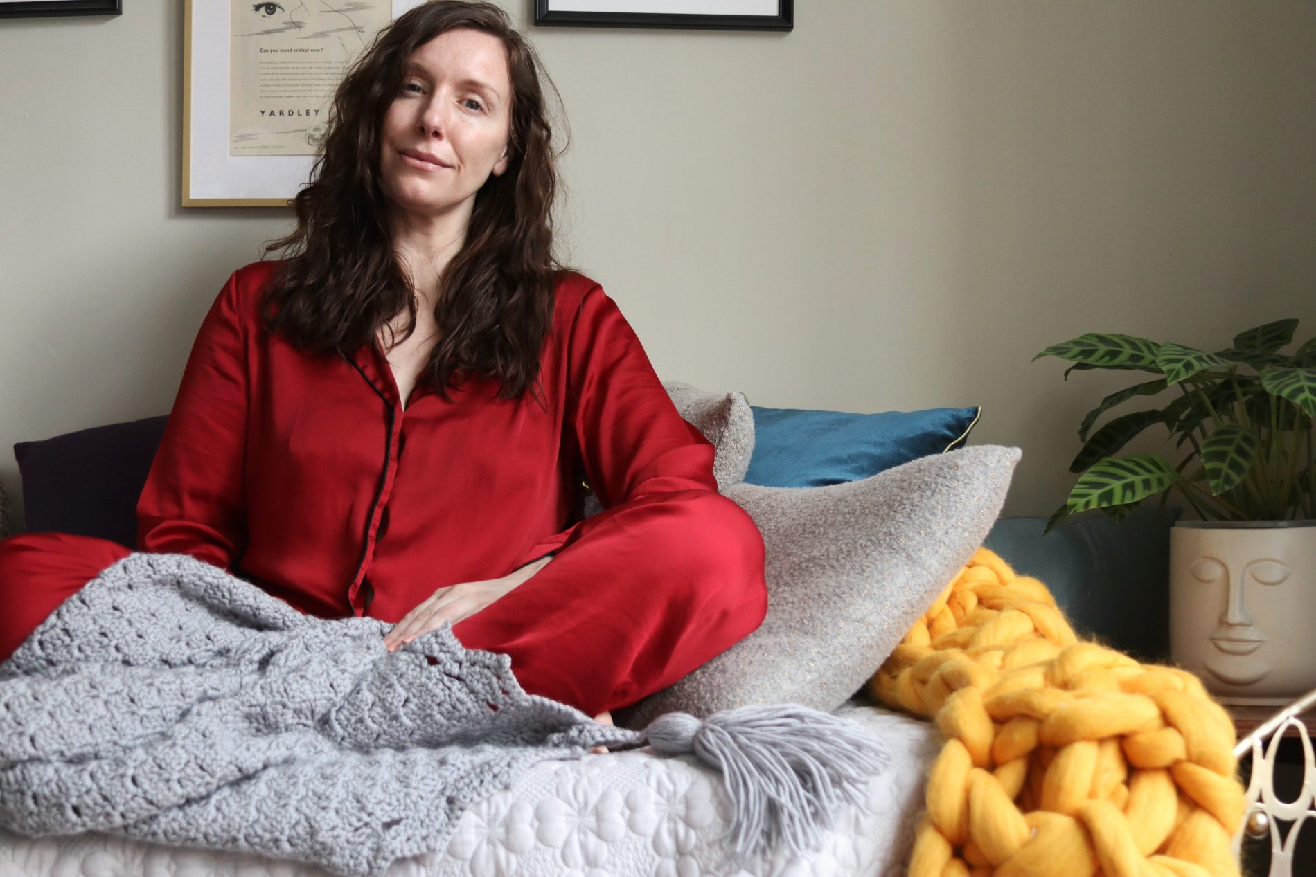 Amy a white female with brown mid length curly hair sits, supported by cushions, crossed legged on her bed covered with a throw. She has multiple invisible illness, chronic illness and is discussing the effects of the covid-19 vaccine in relation to these.