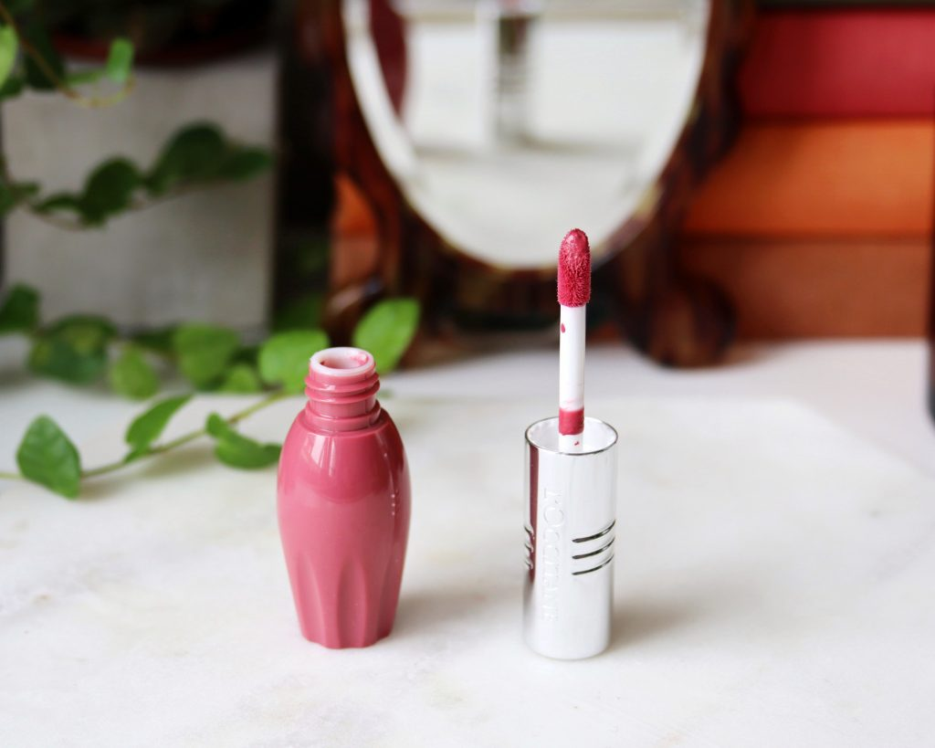 L'occitane Pressed Fruity Lipsticks shade 001 stands open on a marble top. the shade is a nude pink.
