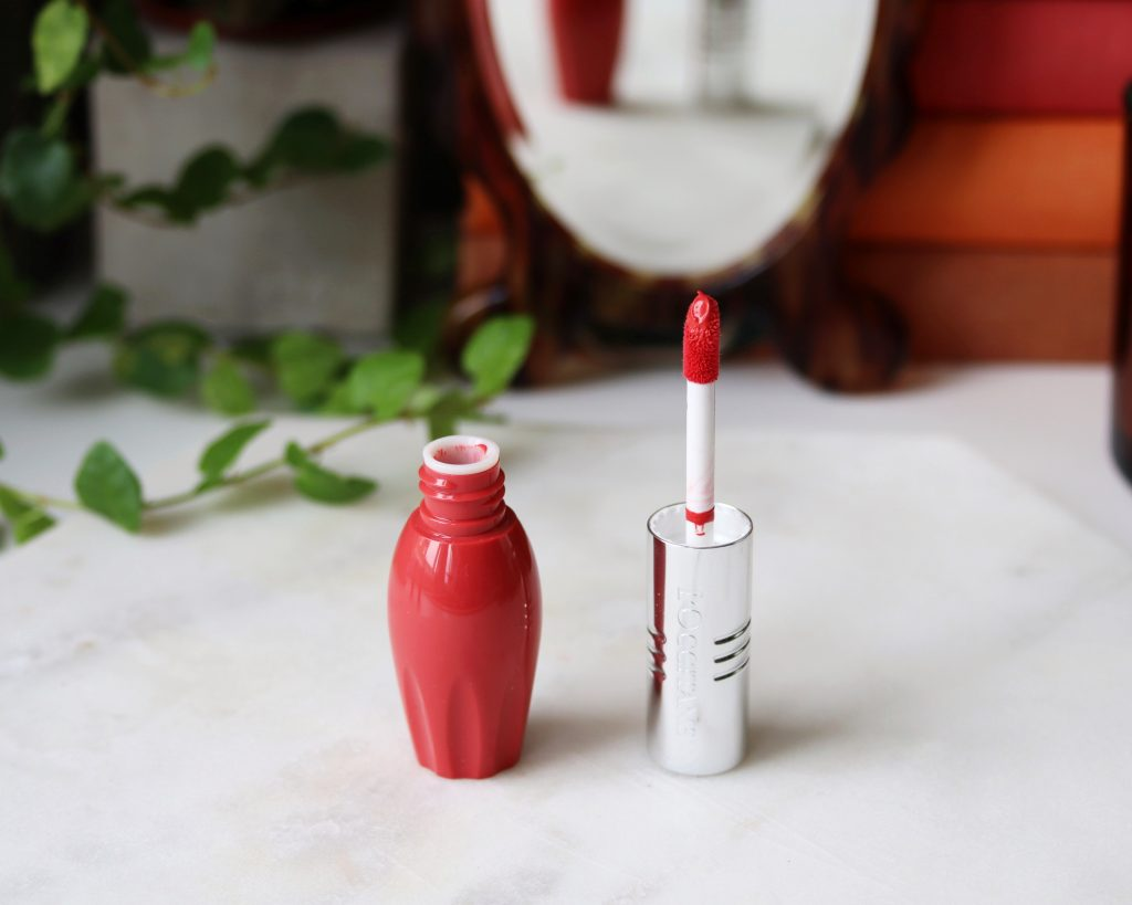 L'occitane Pressed Fruity Lipsticks shade 002 Carrose stands open on a marble top, it is a bright coral pink.