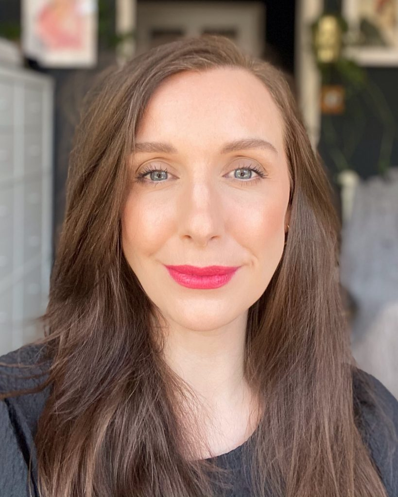 Amy, a makeup artist and beauty blogger with white skin and brunette hair wears the shade 003 Spring Sunrise. It is a nude pink liquid lipstick