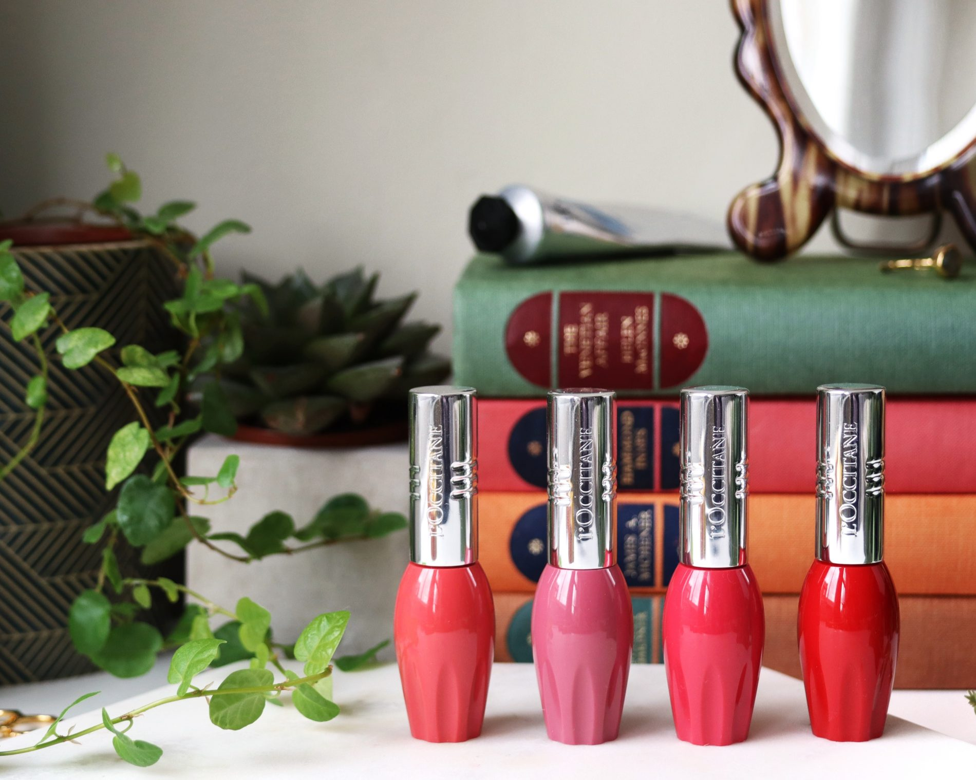 L'occitane Pressed Fruity Lipsticks review and swatches. The four lipsticks are in oval tubes, they are pinks and reds and stand on a marble top.