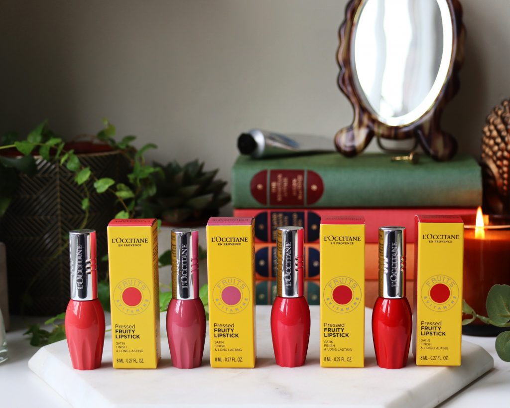 TheL'occitane Pressed Fruity Lipsticks collection with their vibrant yellow packaging stood next to them. This review has swatches and wear tests.