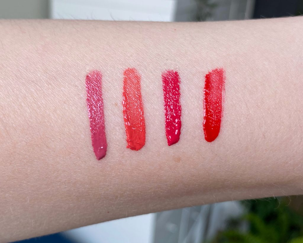 Swatches of theL'occitane Pressed Fruity Lipsticks shades on a white arm. the shades range from pink, coral to red.