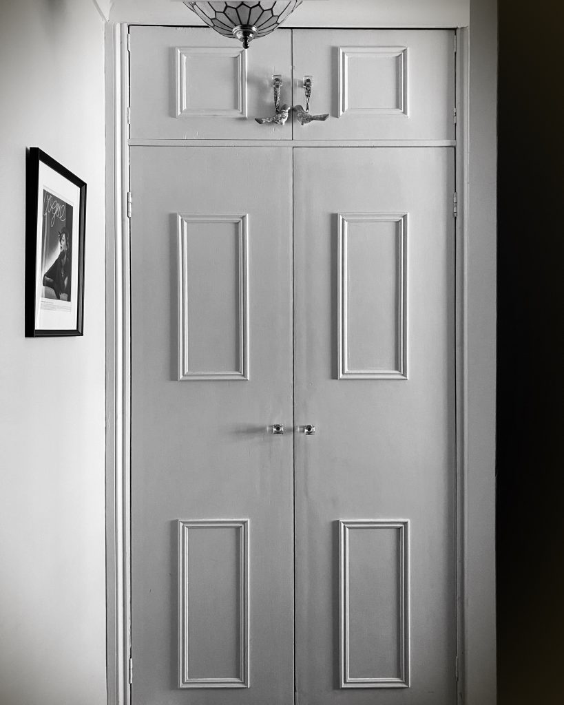 A black and white image of closed wardrobe doors. Signifying clothes unworn due to severe ME/CFS